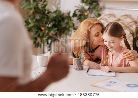 Delightful moments of parenthood. Caring mature loving father enjoying cup of coffee at home and resting while wife enjoying painting with little daughter