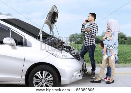 Portrait of an angry father speaking by phone while standing with a broken car and his family on the roadside