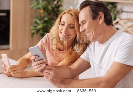 Delighted from being in touch. Delightful harmonious mature couple enjoying free time at home and smiling while using smartphones and sharing happiness