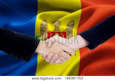 Picture of two people hands in a formal suit shaking hands with Moldova flag background