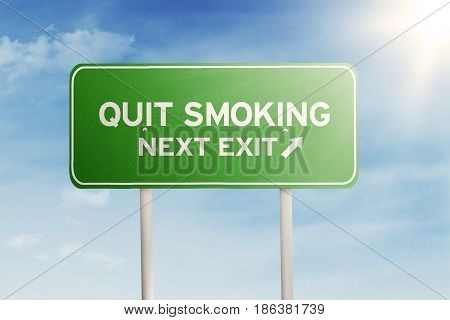 Picture of a green signpost with text of quit smoking and next exit shot under blue sky