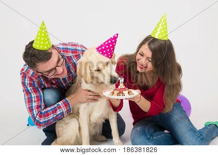 Young couple and a dog retriever in birthday cap. Cake with candle. Closeup portrait over white background
