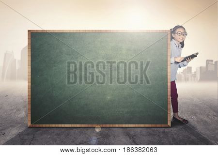 Portrait of little girl student learning with a book while looking at the camera behind a blank chalkboard