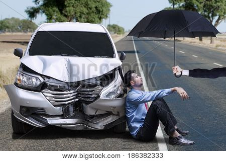 Young businessman sitting next to a dented car under umbrella shot on the road