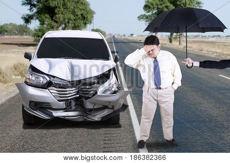Concept of car insurance. Overweight man standing on the road under umbrella with dented car