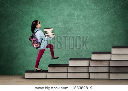 Back to School concept. Nerdy little girl holding a pile of book and carrying backpack while walking on the stair made of book