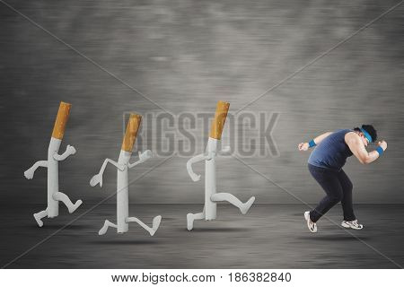 Image of overweight man getting a hallucination while running away by three cigarettes