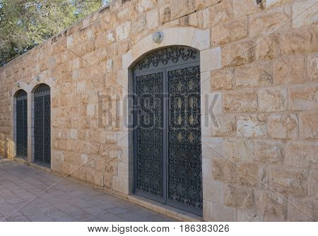 Arched doorways with decorative metal screen in a building made from hewn stone. Building is part of a monastery at Mount Nebo, Jordan near Madaba. Photographed at an angle,