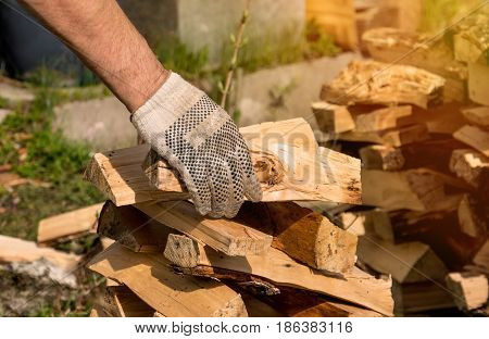 the human hand stacking firewood in a woodpile on green grass in Sunny day, horizontal frame