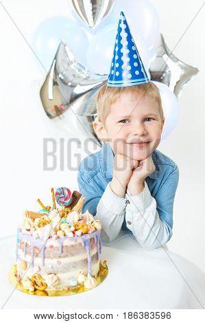 Little blonde boy in festive cap, sit near bithday cake. Concept celebration. Indoor