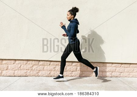Side view of young woman in sportswear jogging near wall
