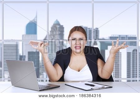 Portrait of young entrepreneur confused with her job while shrugs her shoulder in the office