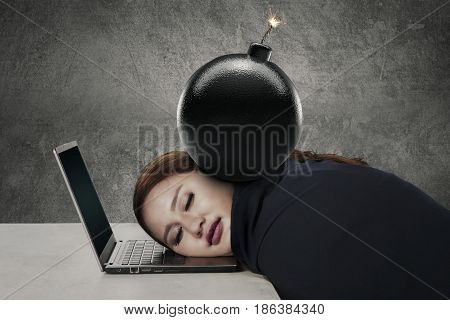 Portrait of young entrepreneur sleeping on her laptop with a bomb over her head