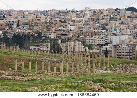 Stone columns and capitals of colonnaded street in the ancient Roman trading city of Jerash, Jordan. The modern city is seen in the background and grassy slopes in the foreground.  Viewed from above.
