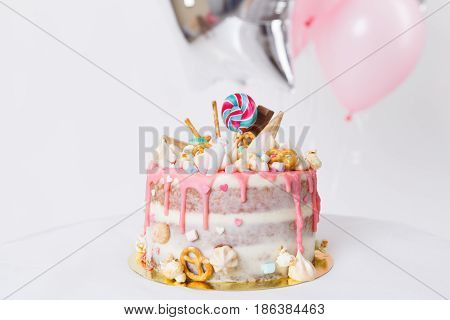 birthday cake with decorated with candies, lollipop, marshmallows. Pink pastel color. Balloons on background. Studio