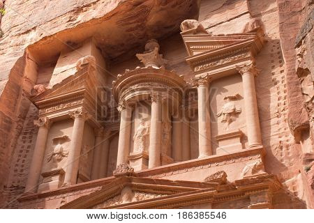 Close up of top of the Treasury, an ancient building in Petra, Jordan. The orange stone with columns carved by Nabataens is one of the Seven Wonders of the World and is a UNESCO World Heritage Site
