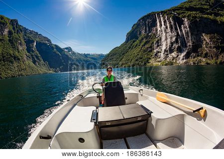 Woman driving a motor boat. Geiranger fjord, Beautiful Nature Norway. Summer vacation.