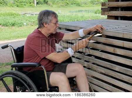 Handicapped carpenter in a wheelchair is building a garden bench