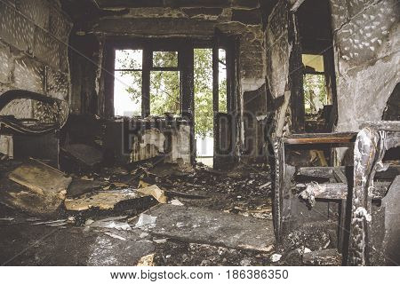 Burned by fire and abandoned room with light from door and window. Consequences of a fire concept