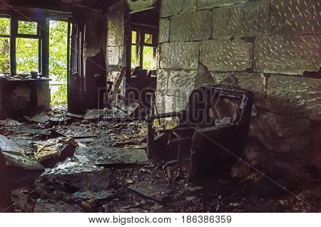 Burned house inside, Burned furniture, interior items, charred walls, windows and doors to the balcony