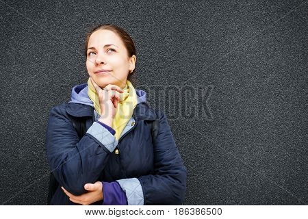 Young cute dreamy woman or girl, smiling and looking up at black textured wall background, copy space