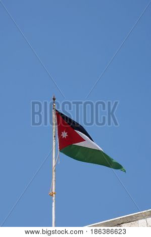 Jordanian flag with Pan-Arab colors of  black, white, and green bands representing the Abbasaid, Umayyad and Fatimid caliphates respectively. Red chevron is for the Hashemite dynasty and Arab Revolt.
