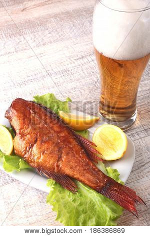 Smoked fish and lemon on green lettuce leaves on Wooden cutting board and glass with beer isolated on white background