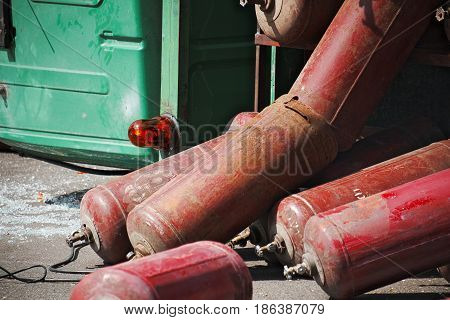 Close-up of scattered gas cylinders and an inverted car