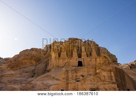 The carved Doric column facade of the Obelisk Tomb, Bab as-Siq, Petra Jordan with the Triclinium beneath it. Photographed from below with blue sky and sun flare above.