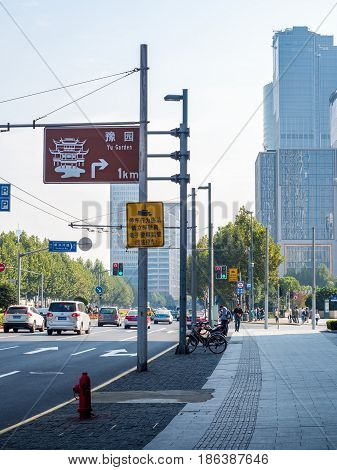 Shanghai, China - Nov 4, 2016: Along Zhongshan East 2nd Road near the intersection of Xinkaihe Road - Traffic and people on wide road. Background high-rise buildings in modern architectural styles. Signboard gives direction to the popular Yu Garden.