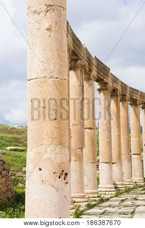 Ancient carved stone columns with ornate capitals and stone lintels or beams curving around the Oval Plaza of Jerash, Jordan. Overcast sky is above and a grassy field in the background.