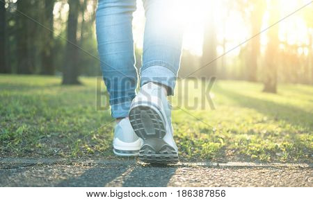 Walking in gray running shoes good for everyday wearing, blue jeans, back to camera