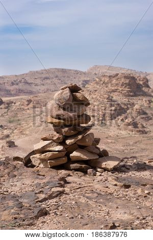 Close up of a cairn on the edge of a cliff near Petra Jordan. Rugged mountains and light blue cloudy sky is in the background.