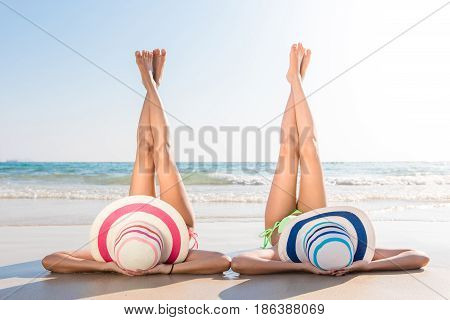 Sexy bikini body asian women enjoy the sea by laying down on sand of beach wearing millinery hat and both legs up in the air. Happy island lifestyle. White sand and crystal sea of tropical beach.
