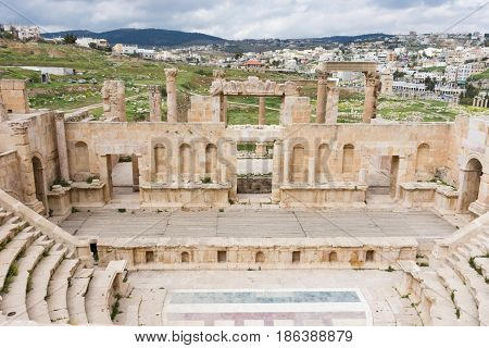 Roman Theater at Jerash, Jordan with view of Jerash city behind the stage in the background and cloudy sky above. The floor of the theater has a mosaic floor.