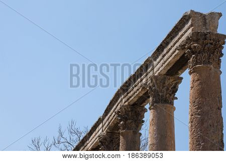 Row of stone columns topped with ornately carved capitals and stone lintel or beams. Ancient ruins are located in Amman Jordan and have blue, cloudless sky in the background. Photographed at an angle.