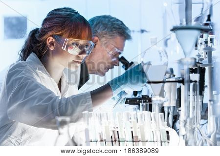 Health care researchers working in life science laboratory. Young female research scientist and senior male supervisor preparing and analyzing microscope slides in research lab.
