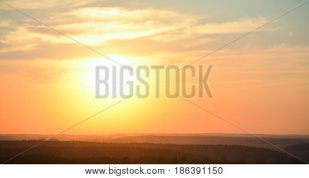 Bright beautifull dramatic sunset with forests. Countryside landscape under ucenic colorful sky at sunset.