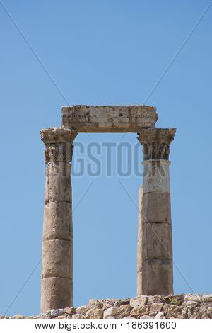Close up of columns of ancient Roman Temple of Hercules with stone beam or lintel on carved capitals at the Citadel against a deep blue cloudless sky.
