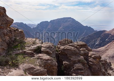 Overlook of a canyon and valley in Jordan near Petra with a rugged blue mountain in the distance, blue cloudy sky above and rocks in the foreground.