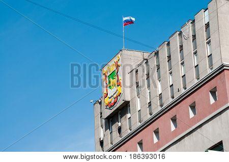 Russia, Vladivostok, April 7: Vladivostok's Coat Of Arms And  Russian Flag On Building