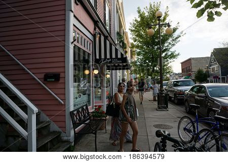 HARBOR SPRINGS, MICHIGAN / UNITED STATES - AUGUST 4, 2016: Pedestrians stroll past Turkey's Restaurant, on Main Street in downtown Harbor Springs, during the evening.