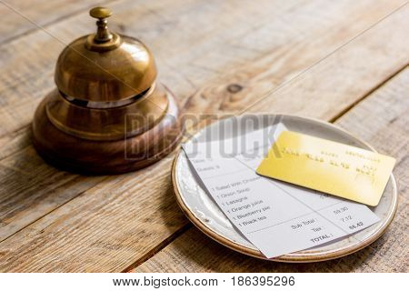 paying check for business lunch in cafe with credit card on wooden table background