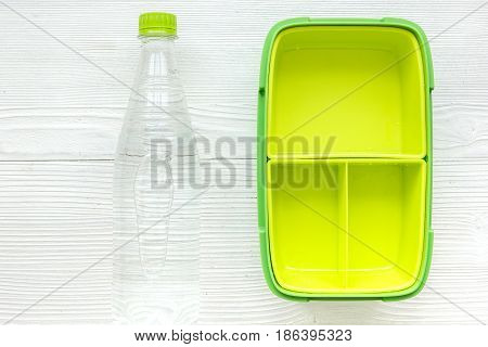 healthy break with bottle of water and green lunchbox on home wooden table background flat lay mock-up
