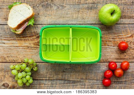 school lunch set with apple and vegetables in lunchbox on wooden table background top view