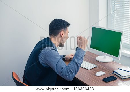 Furious young businessman ready to smash his computer. Chromakey screen with copyspace.