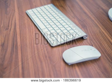 White wireless keyboard and wireless mouse on the wooden table. office concept