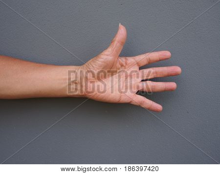 a hand making open the palm of hand on gray background