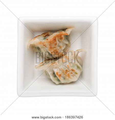 Pan-fried dumplings in a square bowl isolated on white background