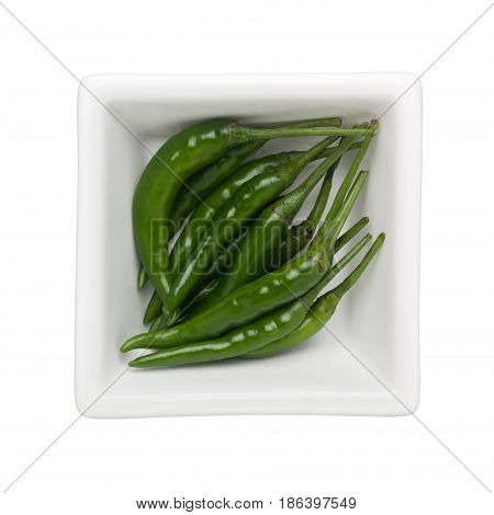 Green chilli in a square bowl isolated on white background